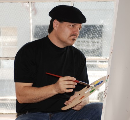 Artist painting on canvas in studio wearing beret and holding paint palette photo