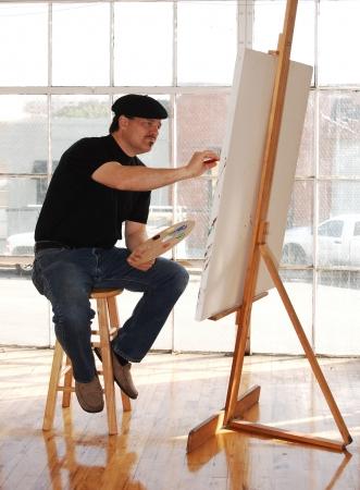 アーティストのベレー帽を身に着けて、ペイント パレットを保持しているスタジオでキャンバスの絵画