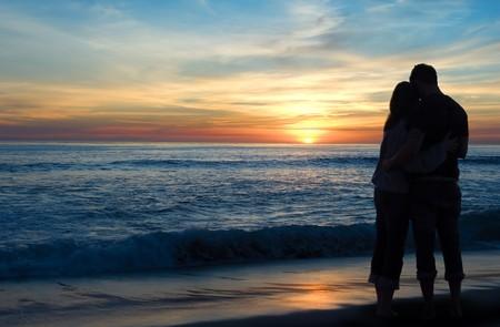Genießen einen romantischen Sonnenuntergang über dem ozean paar
