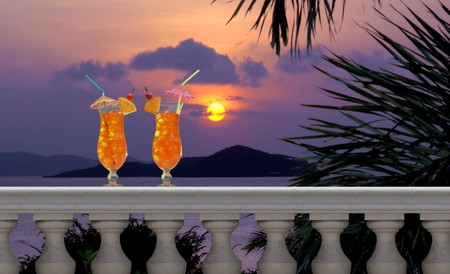 balustrades: Two tropical fruit drinks with straws and umbrellas on a balcony with a tropical sunset in the background Stock Photo