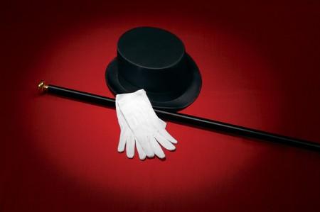caballeros: Sombrero, guantes blancos y ca�a negra sobre fondo rojo bajo un foco Foto de archivo