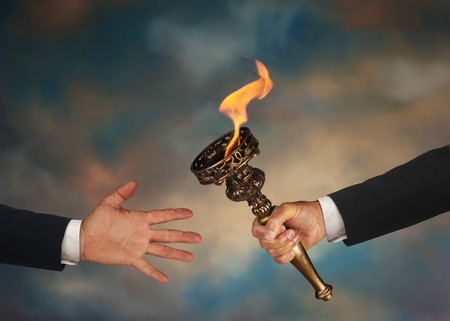 Businessmans outstretched arm passing a flaming torch to another businessmans open hand