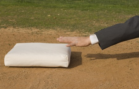 suit  cuff: Arm of a business man about to touch a baseball base in a baseball diamond