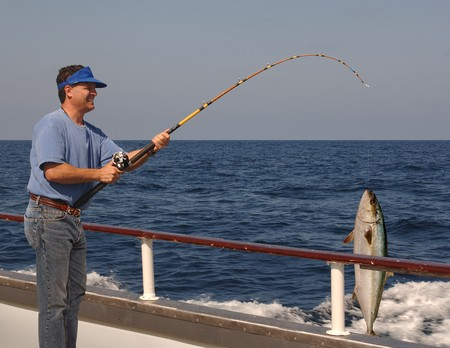 Man fishing from the edge of a moving boat with a live yellow tail tuna hanging from the fishing line