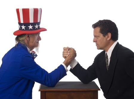 Uncle Sam arm wrestling with a businessman on a white background photo