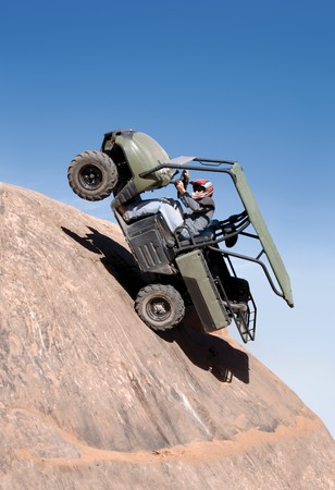 traction: Offroad vehicle climbing up a sheer cliff and falling backwards Stock Photo