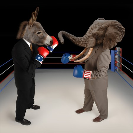 debate: US Republican and Democrat mascots represented by a donkey and an elephant face off in a boxing ring in business suits with red white and blue boxing gloves.