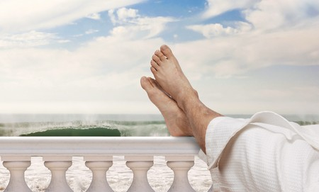 balustrades: man wearing bathrobe resting feet on Italian balustrades with ocean waves in the background Stock Photo