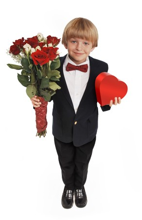 heart suite: 8-year-old boy presenting a heart shaped box of chocolates and a bouquet of roses, wearing a suite and red bowtie on a white background Stock Photo