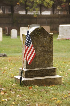 old tombstone at grave of soldier with American flag