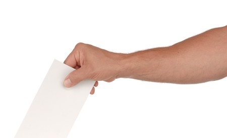 designate: A mans hand putting an envelope in a slot