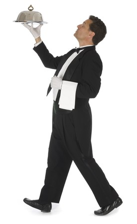 Waiter in a black tuxedo carrying a silver tray with a silver dome on a white background