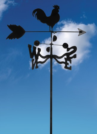 black iron weather vane against blue sky with clouds Imagens