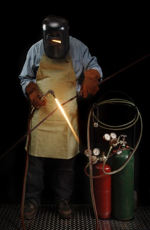 fabricating: Person in protective welding gear heating a piece of metal Stock Photo
