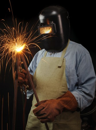 fabricating: Welder torching a piece of steel against a black background Stock Photo