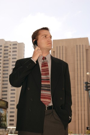 Business executive on a cell phone outside in the heart of the city photo