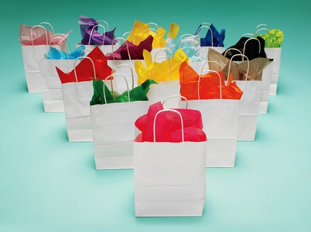 tissue paper: White shopping bags with colorful tissue paper on a teal green background