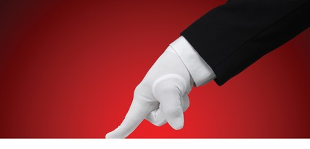 White glove running a finger across a white edge against a red background photo
