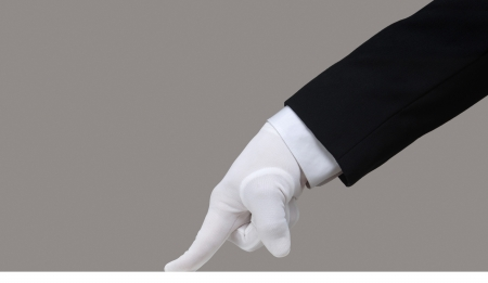 Profile of a white glove running a finger across a clean surface Stock Photo