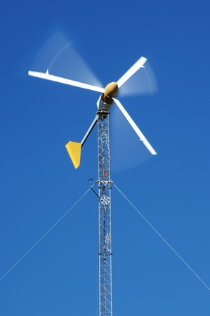 magneto: electric wind turbine generator spinning against blue sky