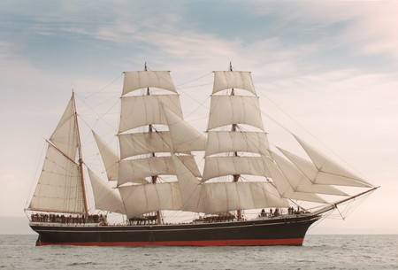 tall ship: Vintage windjammer style ship with full sails on the open sea Stock Photo
