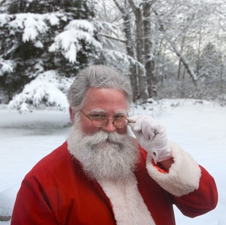 Santa looking over the top of his glasses against a snowy background photo