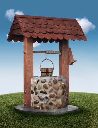 superstitions: Wishing well on grassy hill with blue sky