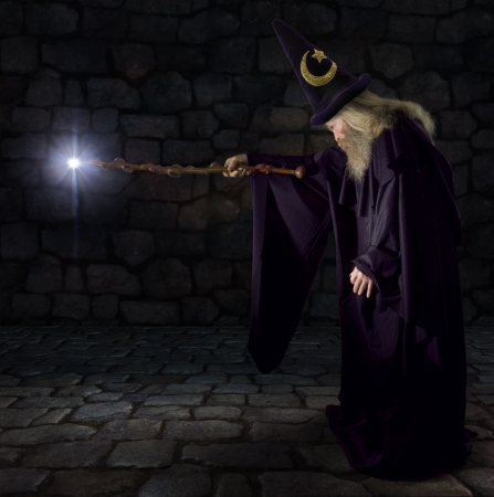 Wizard in a purple robe and wizard hat casting a spell with his wand 스톡 콘텐츠