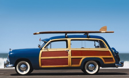 side view of woody car with surfboard and surf in background photo