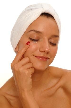 Beautiful woman wearing bath turban, applying eye cream Reklamní fotografie