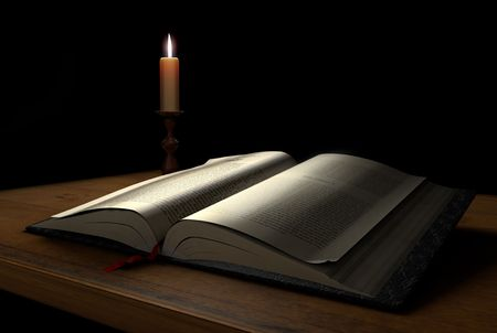candle: An open book on a dark background illuminated with a candle