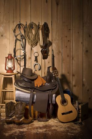 western wall: Still life of cowboy paraphernalia in the tack room of a barn Stock Photo