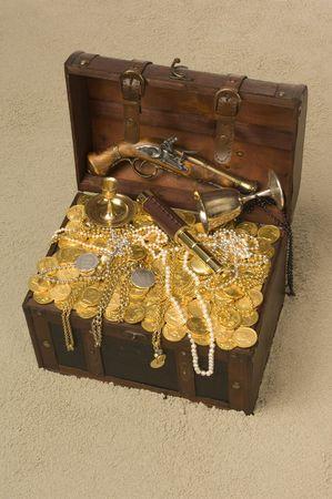 cofre del tesoro: Cofre del Tesoro pirata con la tapa abrir rebosante de oro coings y parafernalia de pirata en una playa de arena