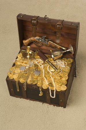 booty: Pirate treasure chest with the lid open brimming with gold coings and pirate paraphernalia on a sandy beach