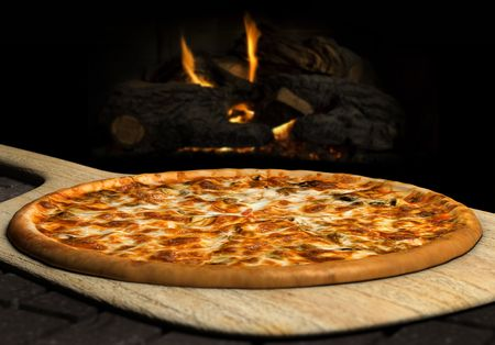 pizza oven: Pizza resting on a pizza peel near an open fire Stock Photo