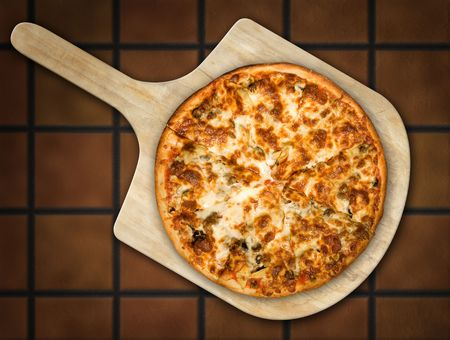 terra cotta: Pizza resting on a wooden pizza peel against a terra cotta tile background