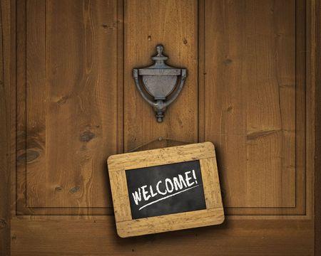 welcome door: Piccola lavagna appesa una porta sotto il battitore porta con la parola Benvenuto scritto in gesso bianco Archivio Fotografico