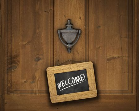 welcome sign: Small chalkboard hanging on a door underneath the door knocker with the word WELCOME written in white chalk