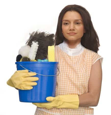 Cleaning lady wearing rubber gloves and an apron holding a bucket of cleaning supplies on a white background