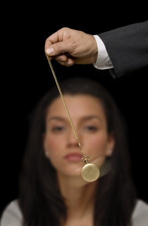 Man's hand holding a pocket watch and swinging it in the fashion of a hypnotist on a black background Banco de Imagens