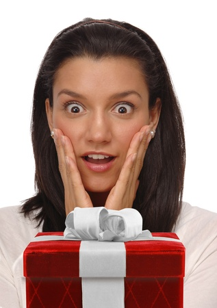 Beautiful, young woman on a white background with an expression of happy surprise staring at a gift box Stock Photo - 9539298