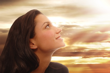 praising god: Joven y bella mujer mirando al cielo con una expresi�n pac�fica