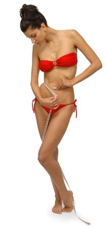 two piece bathing suit: bella, joven mujer comprobar su waitline con una cinta de Totolotl�n en un traje de ba�o de dos piezas Foto de archivo