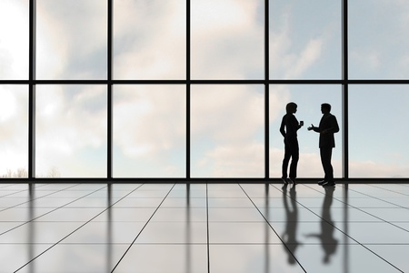 Profielen van twee mensen uit het bedrijfsleven tegen een bank van Vensters in een kantoortoren  Stockfoto