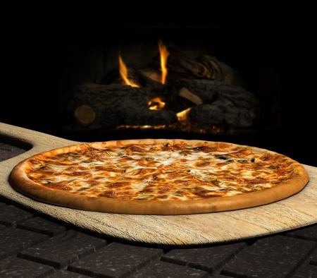 Pizza resting on a pizza peel near an open fire Stock Photo