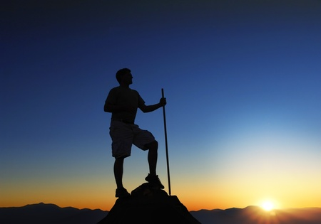 guy with walking stick: Man at the top of a mountain range at sunrise Stock Photo