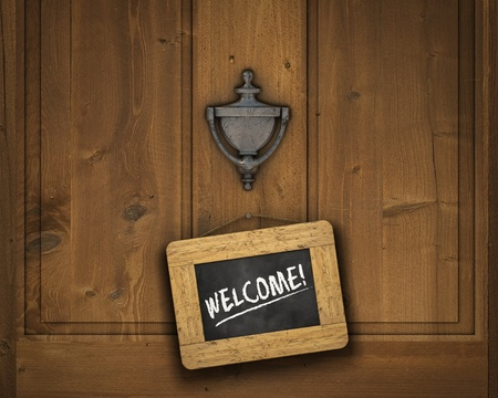 welcome home: Small chalkboard hanging on a door underneath the door knocker with the word