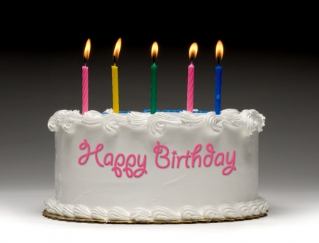 birthday food: White birthday cake profile on graident background with five colorful lit candles and Happy Birthday written on the side with frosting