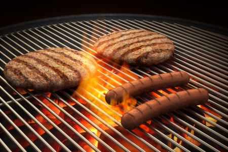 Hamburger patties and hot dogs on the grill under flaming coals photo