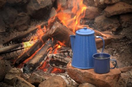 emalj: Emalj coffe potten perkolator och blå emalj kaffekopp vilar på en klippa nära en lägereld